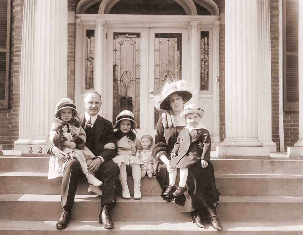 Alvan T. Fuller and family on the steps was taken in Washington, D.C. The date is between 1917-1921, when he was a member of the US House of Representatives.